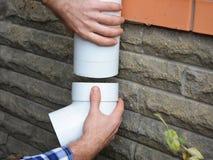 安装塑料雨天沟系统管道的人 Guttering,天沟,塑料Guttering、Guttering &排水设备由杂物工手 库存照片
