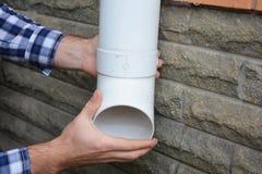 安装塑料雨天沟系统管道的人 Guttering,天沟,塑料Guttering、Guttering &排水设备由杂物工手 免版税图库摄影