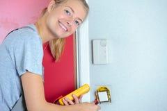 安装壁上插座的女性电工 免版税库存照片
