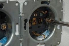 安装壁上插座 拧紧的螺丝 免版税库存照片