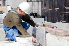 安装大理石瓦片的铺磁砖工 免版税库存照片