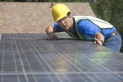 安装太阳电池板的工作者在屋顶 库存照片