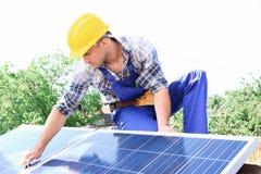 安装太阳电池板的工作者 库存图片