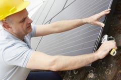 安装太阳电池板的工程师在议院屋顶  免版税库存照片