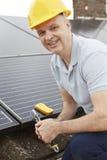 安装太阳电池板的工程师在议院屋顶  库存图片