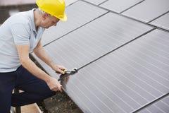 安装太阳电池板的工程师在议院屋顶  免版税库存图片
