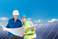 安装太阳电池板的工程师 库存照片