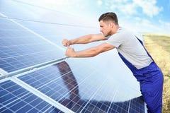 安装太阳电池板的年轻工人 免版税库存照片