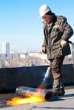安装屋顶毛毡的卷屋面防水工工作者 免版税图库摄影