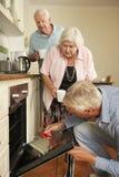 安装工定象烹饪器材在资深夫妇的厨房里 免版税库存照片