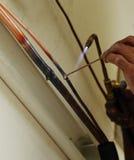 安装工焊接铜管子 库存照片