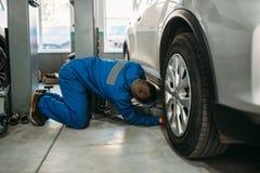 安装工调整在汽车服务的推力起重器 图库摄影