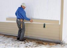 安装房屋板壁的木匠 库存照片