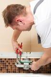 安装搅拌机管道工轻拍的卫生间 图库摄影