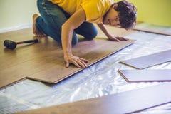 安装新的木层压制品的地板的人 红外地板热 免版税图库摄影