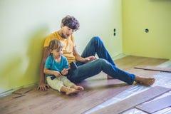 安装新的木层压制品的地板的父亲和儿子 红外 免版税库存照片