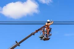 安装新的输电线的电工 免版税库存照片