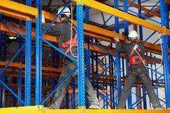 安装机架排列的二名大商店工作者 免版税库存图片