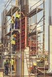 安装混凝土桩模子5的建筑工人 库存图片
