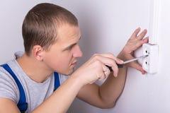 安装电子插口的年轻电工在墙壁 图库摄影