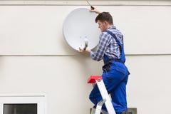 安装电视卫星盘的技术员在墙壁 免版税库存图片