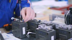 安装电设备,破碎机,电池的无法认出的电工到在工业的电子保险丝箱子里 影视素材
