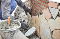 安装石板的泥工工作者在有灰浆的砖墙 库存图片