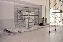 安装石膏墙壁的脚手架的工作者 免版税图库摄影