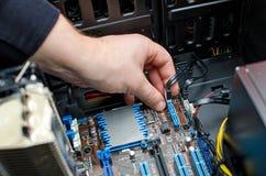 安装硬盘驱动器的技术员的手 库存图片