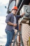 安装空调器的年轻安装工在外壁 免版税库存照片