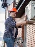 安装空调器的年轻工程师在修筑外壁 库存照片