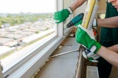 安装窗口的建筑工人 免版税库存照片