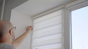 安装窗帘的一位大胆的杂物工的射击的关闭在室内窗口 股票录像