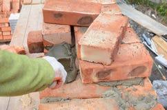 安装红色块和填隙砖石工的瓦工工作者联接有修平刀油灰刀的外墙 砌泥工 免版税库存图片