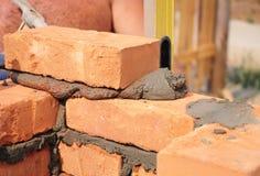 安装红色块和填隙砖石工的瓦工工作者联接有修平刀油灰刀的外部砖房子墙壁 库存照片
