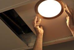 安装聚光灯的电工在厨房天花板 免版税库存照片