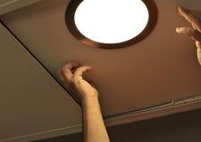 安装聚光灯的电工在厨房天花板 库存图片