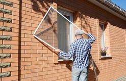 安装蚊子筛网的承包商在房子窗口保护免受昆虫 库存照片