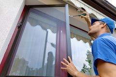 安装蚊帐筛网的人在大阳台门 免版税库存照片