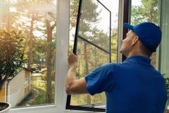 安装蚊帐筛网的工作者在房子窗口 免版税库存照片