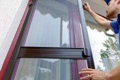安装蚊帐铁丝网的人在房子阳台门 免版税库存照片
