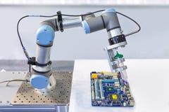 安装计算机芯片的产业机器人在生产线我 免版税库存图片