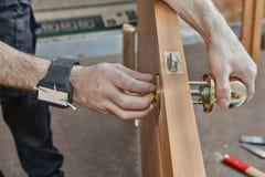 安装门把手,人的hend举行doorha的关闭的木匠 免版税库存照片