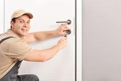 安装门锁的快乐的锁匠 库存照片