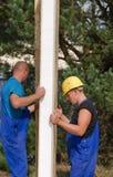 安装绝缘材料的工作员在建筑工地 免版税库存图片
