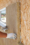 安装绝缘材料的建造者工作者在墙壁 库存照片