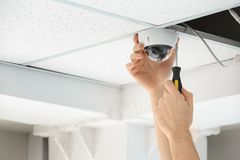 安装CCTV照相机的技术员在室内天花板 免版税库存照片