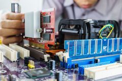 安装VGA卡片的技术员的手 免版税库存照片