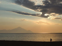 安静的早晨,海滩的孤独的渔夫 免版税图库摄影