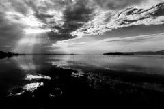 完全一个湖的相称和壮观的看法,有云彩的,天空和太阳发出光线反射在水 库存图片